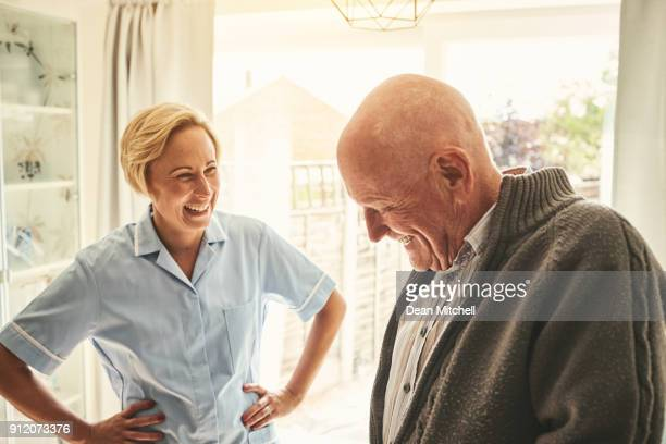 smiling senior man and female carer at home - nursing assistant stock pictures, royalty-free photos & images