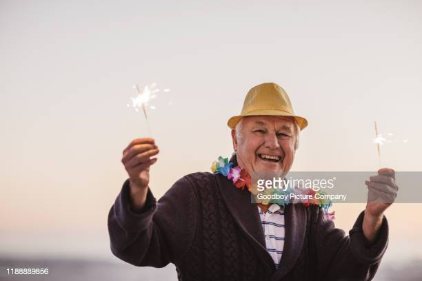 smiling senior man celebrating new year's with sparklers at sunset - 70 year old man stock pictures, royalty-free photos & images