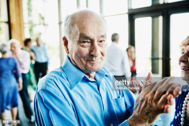 Smiling senior man clapping after dancing with wife in ballroom