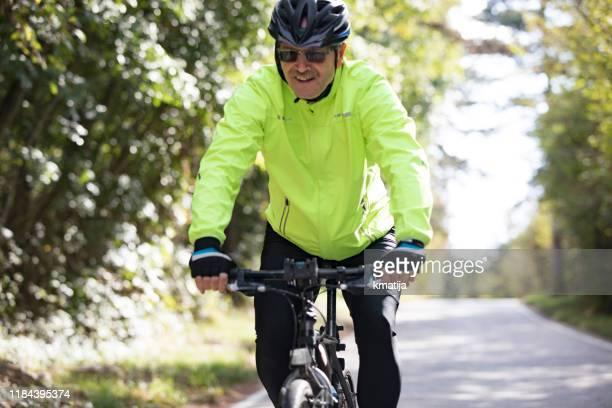 カントリーロードで笑顔のシニアマンサイクリング - リフレクター ストックフォトと画像