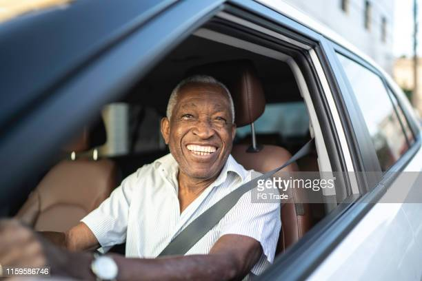 smiling senior man driving a car and looking at camera - taxi driver stock pictures, royalty-free photos & images