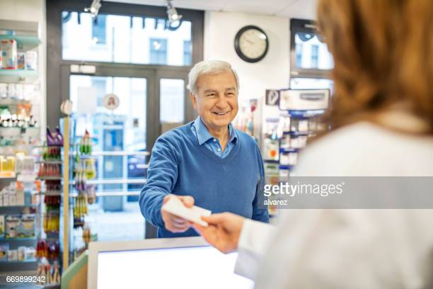 Smiling senior man giving prescription to chemist