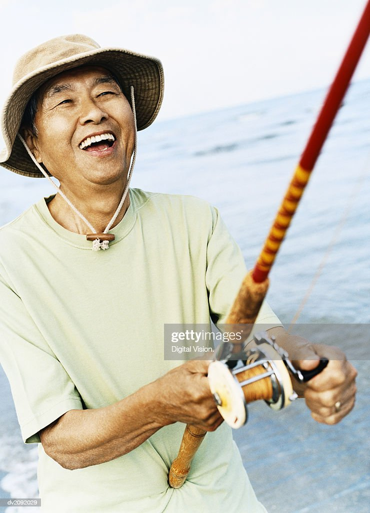 Smiling Senior Man Holding a Fishing Rod : Stock Photo