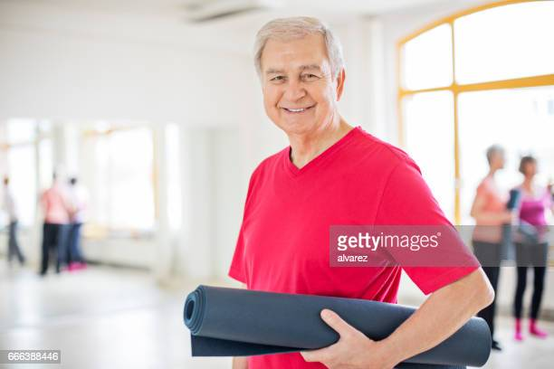 lächelnd senior woman holding übung matte in der klasse - einzelner senior stock-fotos und bilder