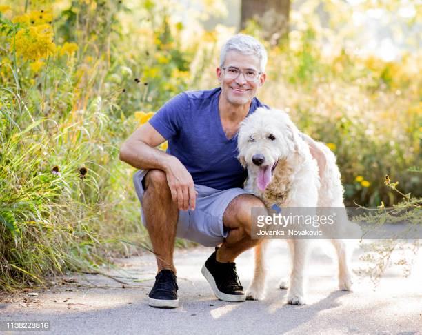 smiling senior man hugging dog - hairy old man stock pictures, royalty-free photos & images