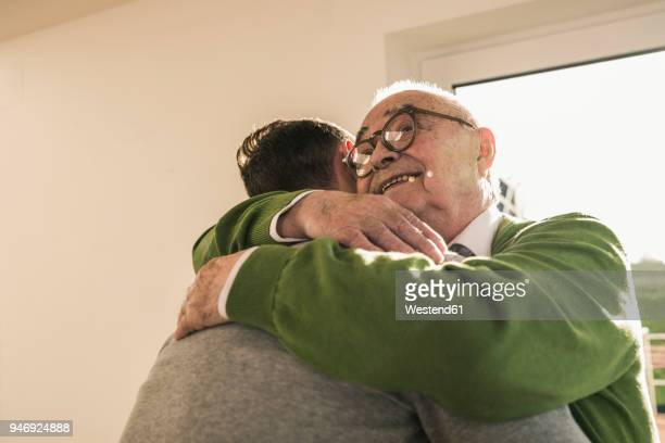 smiling senior man hugging young man - visit stock pictures, royalty-free photos & images