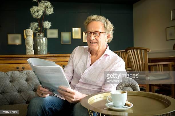 Smiling senior man in lounge room reading magazine