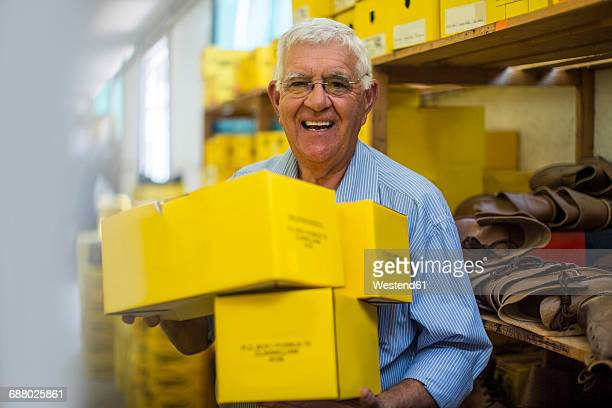 smiling senior man in warehouse carrying shoe boxes - shoe box stock pictures, royalty-free photos & images