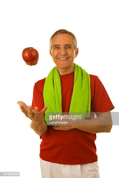 Smiling senior man in workout attire tossing red apple