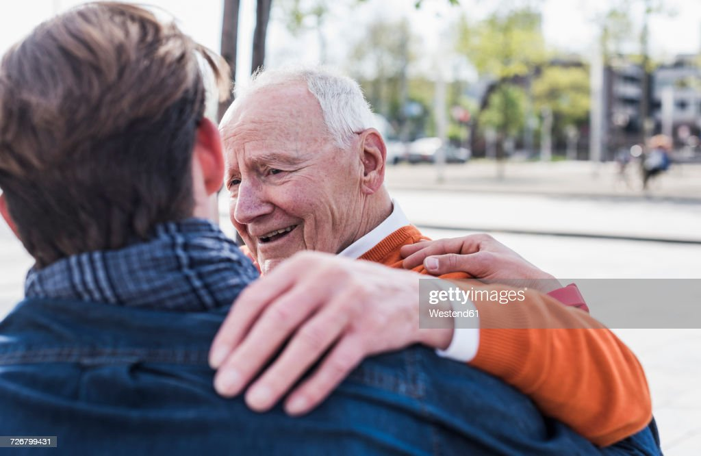 Smiling senior man looking at adult grandson outdoors : Stock Photo