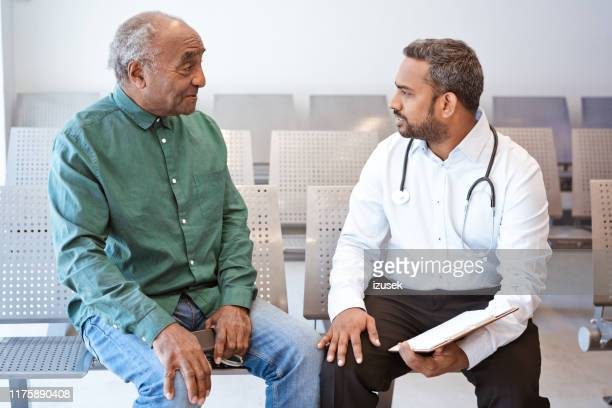 smiling senior man looking at doctor in hospital - outpatient care stock pictures, royalty-free photos & images