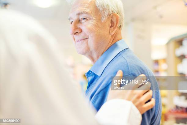 smiling senior man looking at pharmacist - hand on shoulder stock pictures, royalty-free photos & images