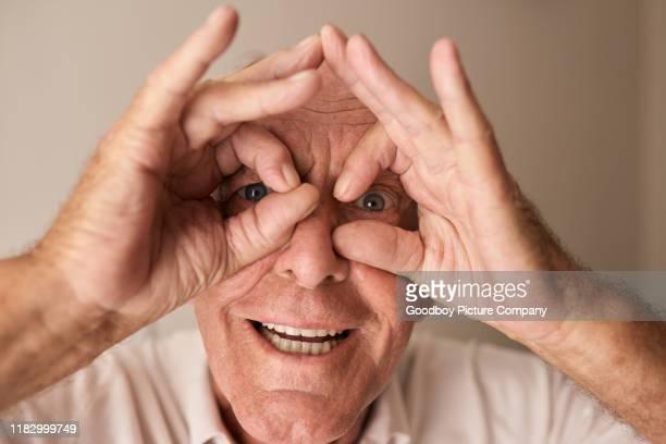 指のメガネを通して見ている笑顔の先輩 - チラッと覗く ストックフォトと画像