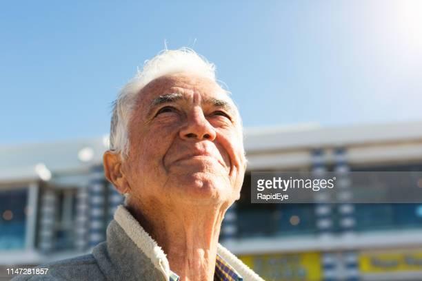 glimlachende senior man kijkt omhoog naar sky, ontspannen en tevreden - huidkanker stockfoto's en -beelden