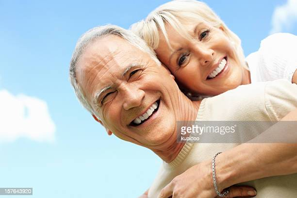 Smiling senior man piggybacking a mature woman against sky