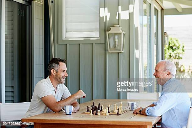 Smiling senior man playing chess with son