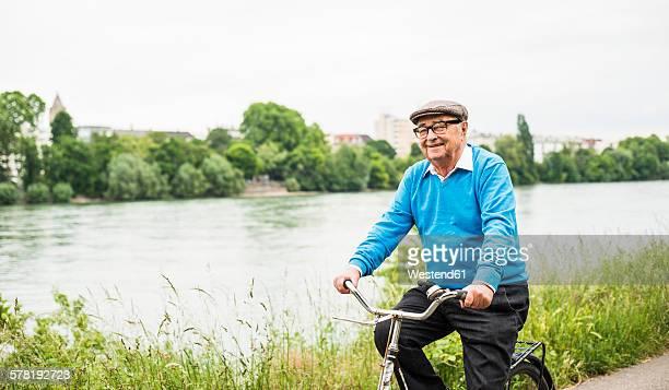 Smiling senior man riding bicycle