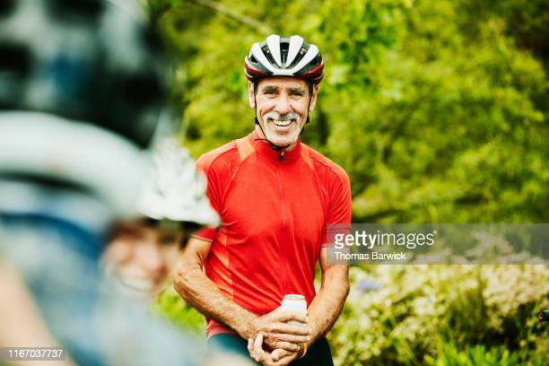 smiling senior man sharing beers with friends after mountain bike ride - sportsperson stock pictures, royalty-free photos & images