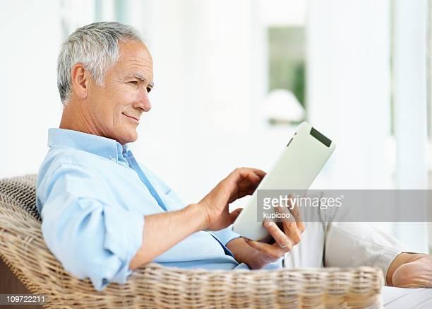 Sorridente homem idoso sentado no sofá segurando um tablet PC