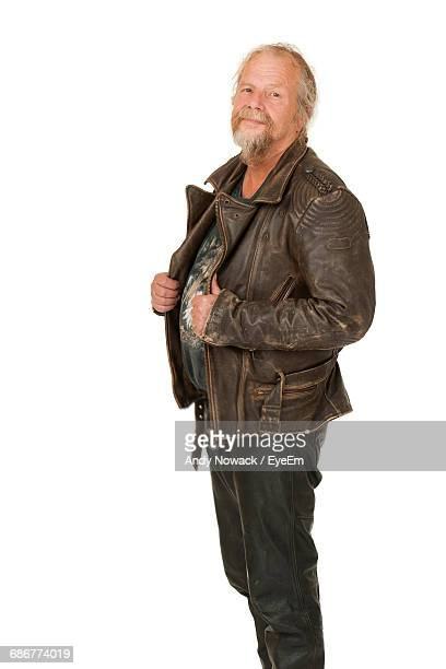Smiling Senior Man Standing In Leather Jacket Against White Background
