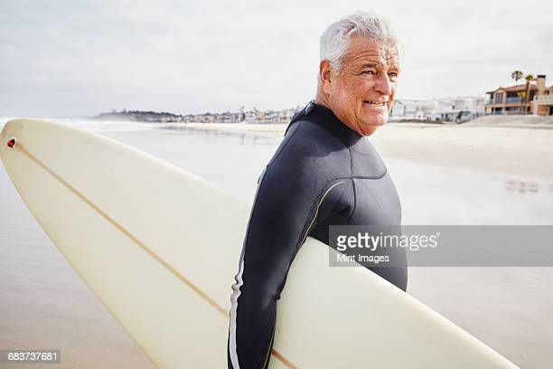 smiling senior man standing on a beach, wearing a wetsuit and carrying a surfboard. - wetsuit stock pictures, royalty-free photos & images