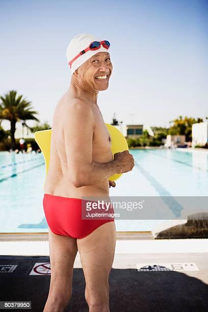Smiling senior man swimmer at pool