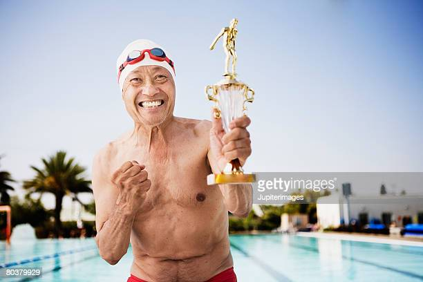 smiling senior man swimmer holding trophy - disruptagingcollection stock photos and pictures