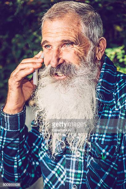 Smiling Senior Man Talking on Mobile Phone in his Backyard