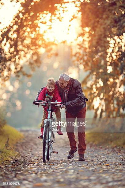 Smiling senior man teaching his grandchild how to cycle.