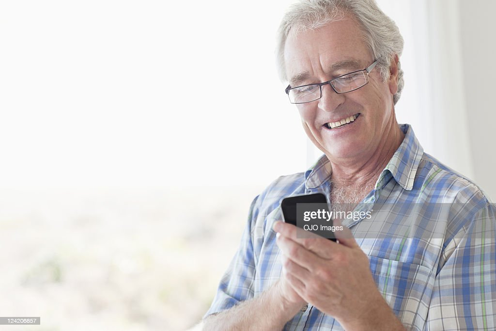 Smiling senior man texting using smart phone : Stock Photo