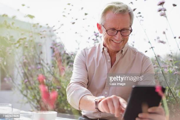 Smiling senior man using digital tablet on patio