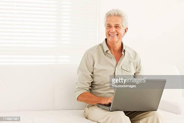 Sonriente hombre senior utilizando portátil en casa