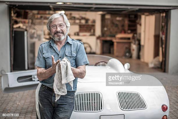 smiling senior man with cleaning cloth leaning at sports car - freizeitaktivität stock-fotos und bilder