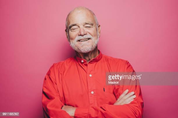 smiling senior man with eyes closed against pink background - augen geschlossen stock-fotos und bilder