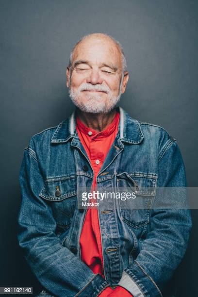 Smiling senior man with eyes closed standing against gray background