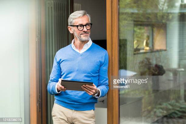 smiling senior man with grey hair standing in front of his modern design home holding tablet - ricchezza foto e immagini stock
