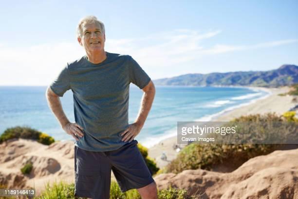 smiling senior man with hands on hips standing on cliff at beach against sky - handen på höften bildbanksfoton och bilder