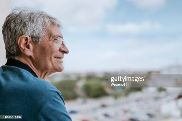 smiling senior man with hearing aid outdoors - hearing aid stock pictures, royalty-free photos & images