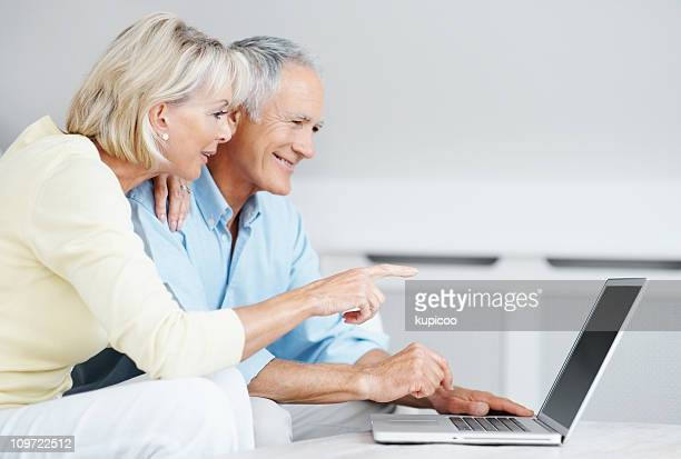 Smiling senior man with mature woman pointing at laptop screen