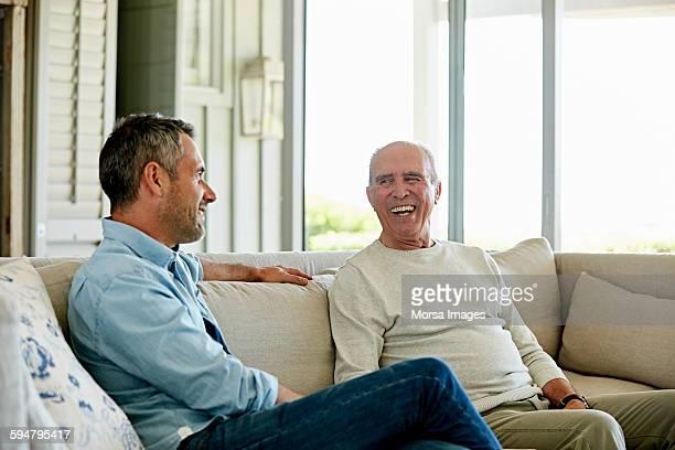 Smiling senior man with son sitting on sofa