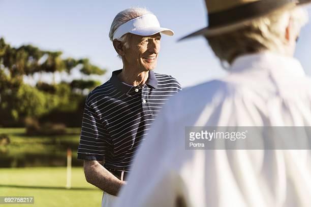 Smiling senior man with woman wearing sun visor