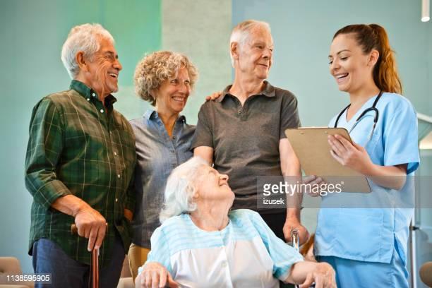 uomini e donne anziani sorridenti che guardano l'infermiera - izusek foto e immagini stock