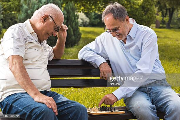 Smiling senior men playing chess in the park.