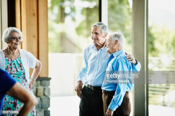 Smiling senior men standing in community center with arms around each other