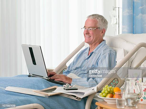 Smiling senior patient in bed using laptop at hospital