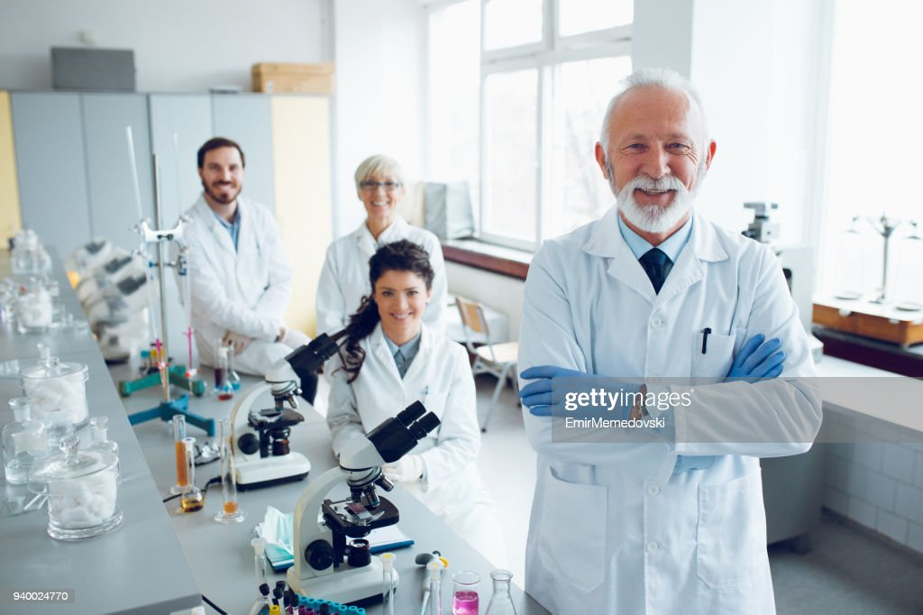 Smiling senior scientist with his colleagues in laboratory : Stock Photo
