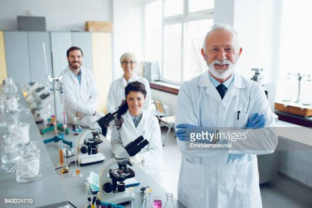 Smiling senior scientist with his colleagues in laboratory