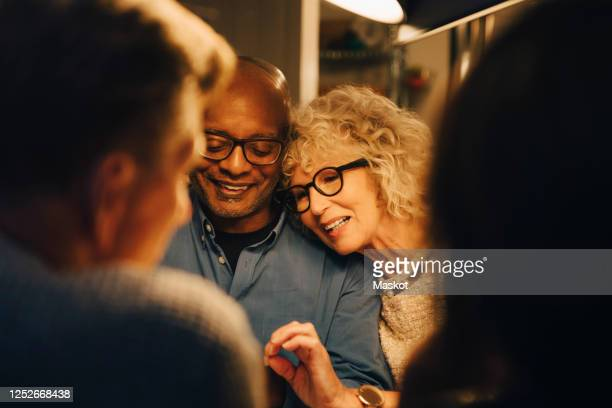 smiling senior sharing smart phone with woman while sitting at illuminated dining table - mensen op de achtergrond stockfoto's en -beelden