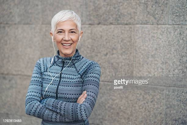 smiling senior sportswoman standing with arms crossed - white hair stock pictures, royalty-free photos & images