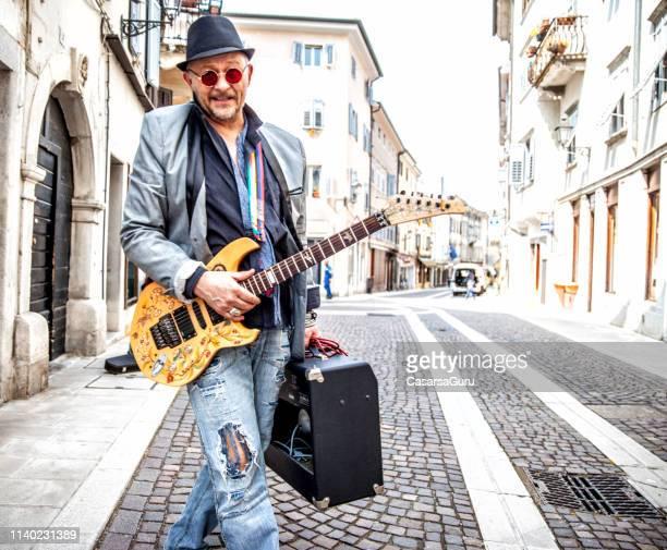 街の通りを歩いているシニアストリートギタリストの笑顔 - アンプ ストックフォトと画像